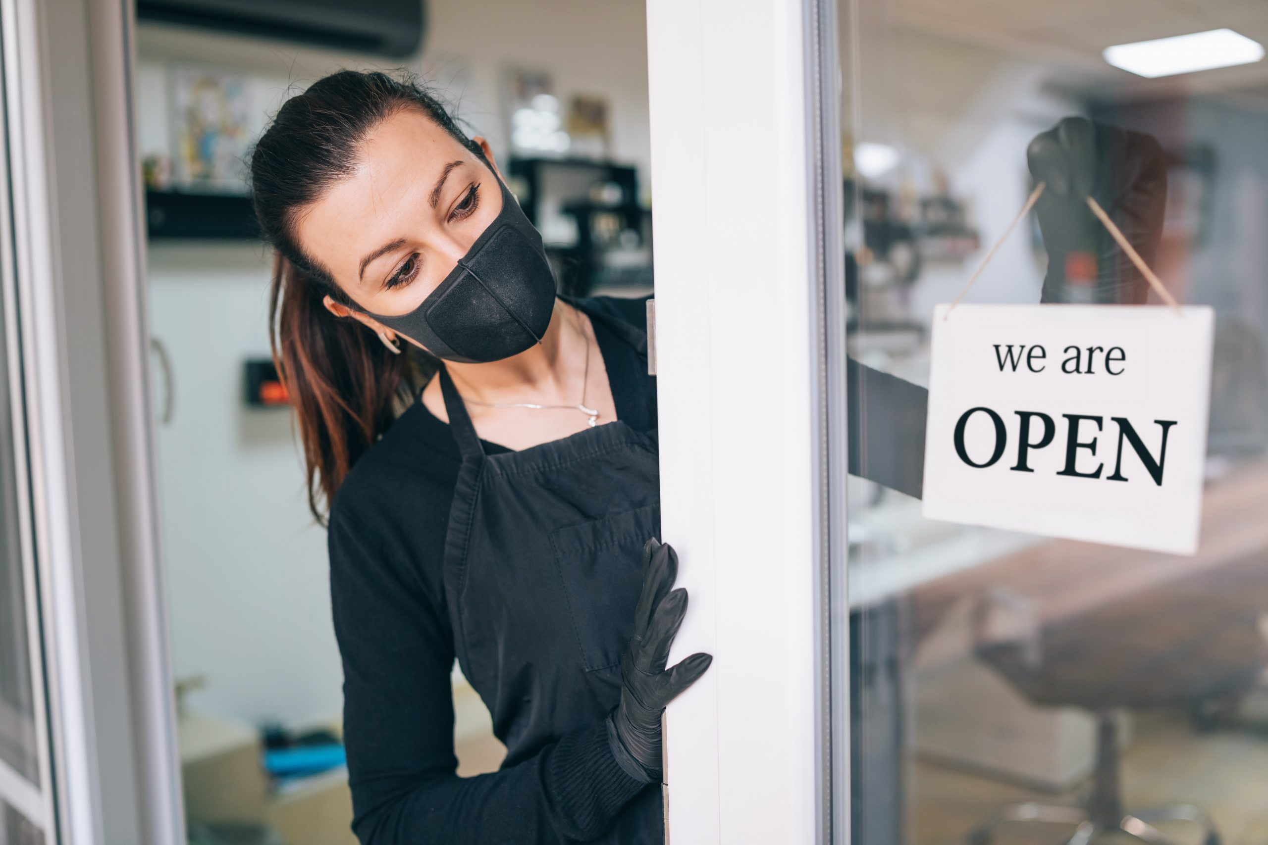 "Business owner wearing face covering and gloves holds ""We are open"" sign"